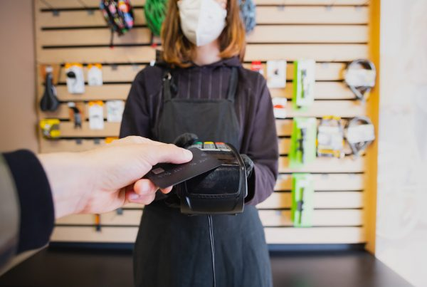 Person paying with credit card at a local retail shop
